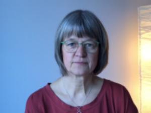 Bilden föreställer logoped Hanne Uddling. Hon har röd tröja, glasögon och blont halvlångt hår med lugg.